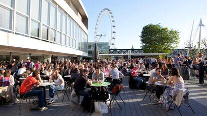 People enjoying drinks in the sun at the Royal Festival Hall Terrace Bar, Southbank Centre